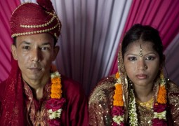 "13 year old Runa Akhter sits next to her husband, 29 year old Zahrul Haque Kajal, the day of her wedding, August 29, 2014 in Manikganj, Bangladesh. Runa was in the 7th grade, and loved reading, sports and traveling. She wanted to wait until she was 21 to get married but, ""No boy want's to marry a girl older than 18 in my village"" she said. In June of this year, Human Rights Watch released a damning report about child marriage in Bangladesh. The country has one of the highest rates of child marriage in the world, with 29% of girls marrying before the age of 15, and 65% of girls marrying before they turn 18. The detrimental effects of early marriage on a girl cannot be overstated. Most young brides drop out of school. Pregnant girls from 15-20 are twice as likely to die in childbirth than those 20 or older, while girls under 15 are at five times the risk. Research cites spousal age difference as a significant risk factor for violence and sexual abuse. Child marriage is attributed to both cultural tradition and poverty. Parents believe that it ""protects"" girls from sexual assault and harassment. Larger  dowries are not required for young girls, and economically, women's earnings are insignificant as compared to men's."